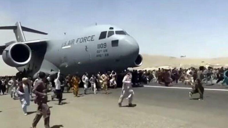 16일(현지시간) 아프가니스탄 수도 카불의 하미드 카르자이 국제공항에서 미군 C-17 수송기가 이륙을 위해 활주로를 따라 이동하자 탑승하지 못한 아프간 시민 수백 명이 수송기를 따라 내달리고 있다. 탈레반이 정권 재장악을 선언하자 카불 국제공항에는 외국으로 탈출하려는 시민들이 끝도 없이 몰려들었으며 결국 항공기 운항이 중단되고 공항은 마비됐다.   AP/연합