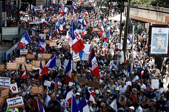 14일(현지시간) 프랑스 파리에서 중공 바이러스 감염증(코로나19) 백신 접종 증명서 확대 정책에 반대하는 시민들이 거리에서 항의하고 있다.   SAMEER AL-DOUMY/AFP via Getty Images/연합