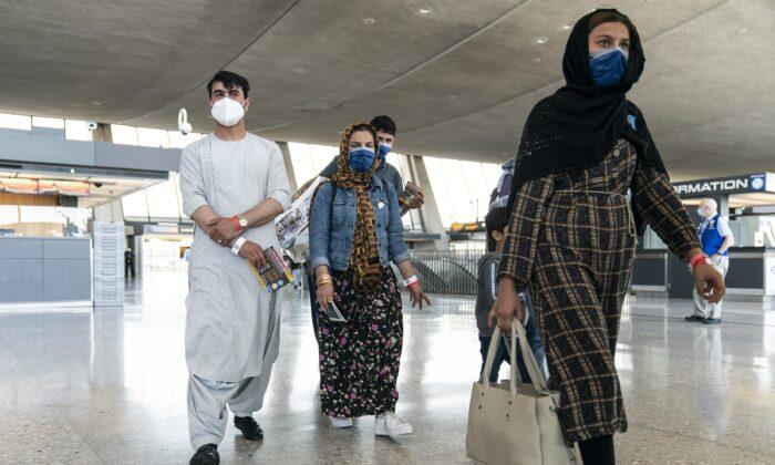 24일 아프가니스탄의 한 가족이 미국 버지니아주 둘레스 국제공항의 수속 구역으로 가는 버스로 향하고 있다. | Joshua Roberts/Getty Images