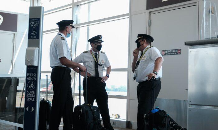 조종사들이 미국 버지니아주에 위치한 로널드 레이건 워싱턴 내셔널 공항에서 대화를 나누고 있다. 2020.7.22   Michael A. McCoy/Getty Images