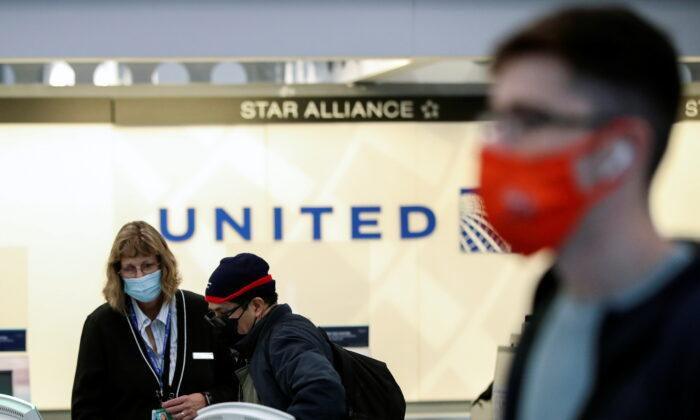 미국 시카고 오헤어국제공항의 유나이티드항공 티켓 카운터에서 직원이 고객의 탑승권 발급을 돕고 있다. 2020.11.25 | Kamil Krzaczynski/Reuters/ 연합