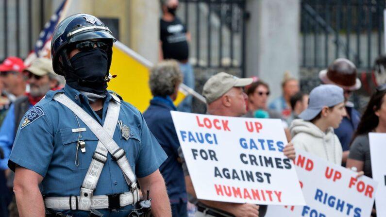 미국 매사추세츠 주민들이 주의사당 앞에서 마스크 의무화 조치에 반대하는 시위를 벌이는 가운데, 경찰이 주변을 지키고 있다. | JOSEPH PREZIOSO/AFP via Getty Images
