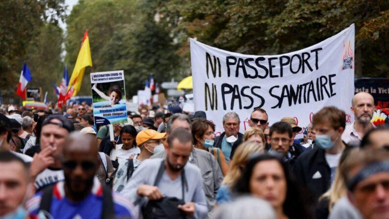파리의 한 거리에서 시위대가 중공 바이러스 감염증(코로나19) 백신 여권에 반대하는 시위를 벌이고 있다. '(백신) 여권도 없고, 건강증도 없다'고 쓴 현수막이 보인다. | THOMAS SAMSON/AFP via Getty Images