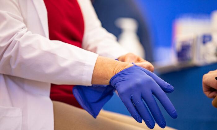 캘리포니아주 세인트 조셉 병원의 한 의료진이 의료용 장갑을 착용하고 있다. 2020.12.16 | John Fredricks/The Epoch Times