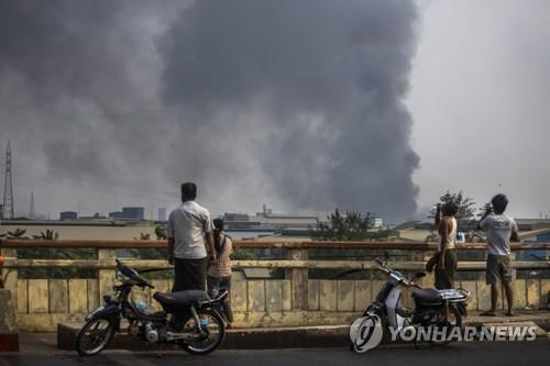 14일 미얀마 양곤에서 불타는 중국계 공장. 중국 정부의 자작극이라는 주장이 제기됐다. | AP 연합