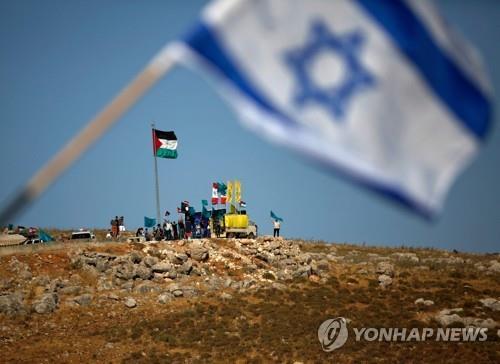 이스라엘 북부 국경에 내걸린 이스라엘 국기 뒤로 레바논에서 레바논 국기와 팔레스타인, 헤즈볼라 깃발을 세우고 반이스라엘 시위를 벌이는 사람들. | AFP/연합뉴스