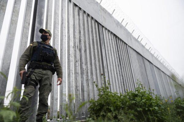 그리스와 터키 국경지대를 흐르는 에브로스강 인근 국경 장벽 옆을 한 경찰관이 순찰하고 있다. 2021.5.21   Giannis Papanikos/AP Photo/연합